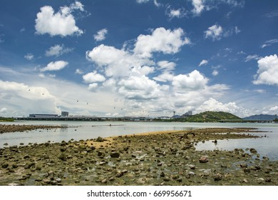 Shingle beach in Tung Chung, Hong Kong. Hong Kong international airport and Ngong Ping 360 are also shown in here. Wide angle background eith blue cloudy sky and wetland.
