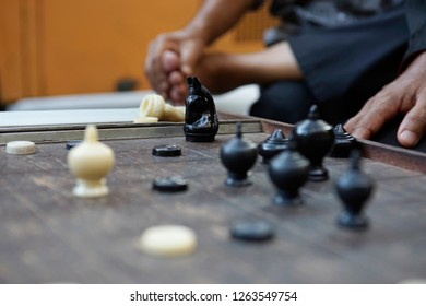 A shining black knight on a wooden Thai chessboard