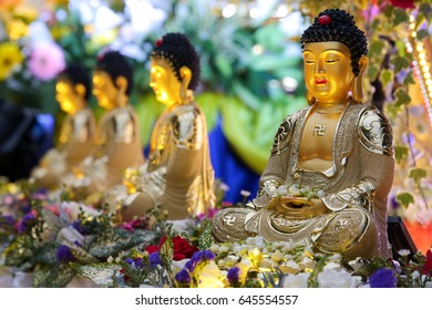 Shining buddha statues decorating a Wesak day procession floats.