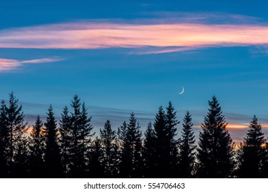 Shining clouds and crescent moon in evening sky