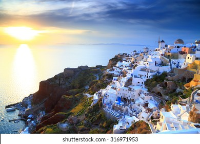 Shining light illuminates traditional white buildings on the Oia village and the sea, Santorini island, Greece