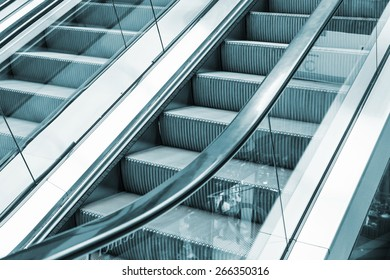 Shining metal escalator moving up, blue toned monochrome photo, selective focus with shallow DOF
