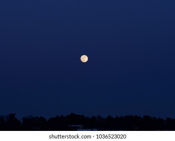 A shining moon over the dark sky during the winter days, Espoo, Finland