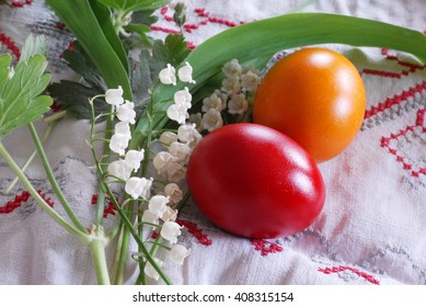 shining red and orange Easter eggs with lily of the valley plant