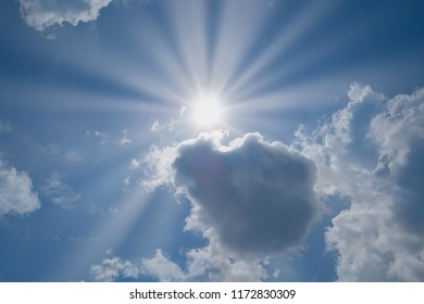 Shining sun half hide by clouds. Beautiful blue sky with sunbeams and clouds. Sun rays over all the image.