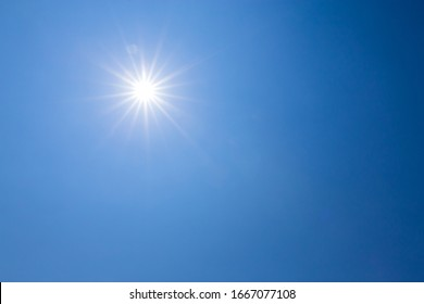 Shining sun on clear blue sky. lens flare of sunlight on blue sky background. Bright sun on blue sky.