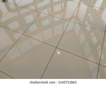 Shining tiles floor surface with windows reflection.