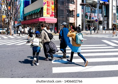 Shinjuku, Japan - April 2, 2019: People walking crossing stree to famous Kabukicho alley street in downtown city during day with colorful signs