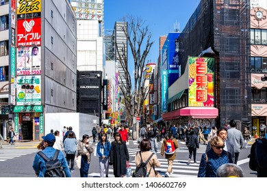 Shinjuku, Japan - April 2, 2019: People walking on famous Kabukicho alley street in downtown city during day with colorful signs