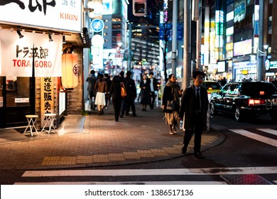 Shinjuku, Japan - April 3, 2019: Tokyo district downtown city with night evening and people walking on sidewalk by restaurants after work
