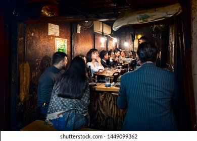 Shinjuku, Japan - April 4, 2019: Memory lane alley with izakaya and people sitting, drinking and eating by sidewalk in Tokyo city at night, chef cooking yakitori grilled chicken food