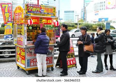 SHINJUKU, TOKYO - DECEMBER 6, 2014: Lines of people for buying the biggest lottery in Japan, Nenmatsu Jumbo or Year end Jumbo lottery.