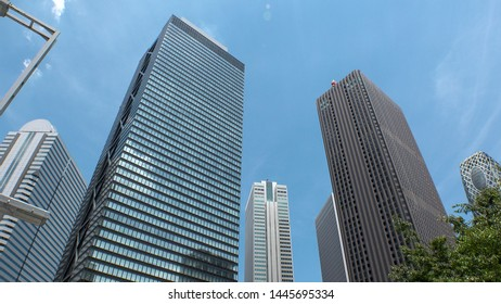SHINJUKU, TOKYO, JAPAN - CIRCA JUNE 2019 : View of looking up tall modern buildings and sky in day time. Famous business district in Tokyo, where many company office buildings are located.