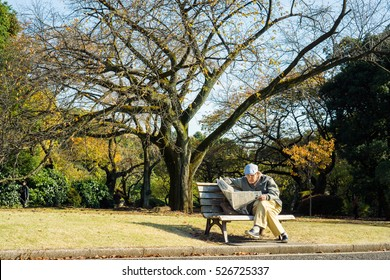Shinjuku Tokyo, Japan : Nov 26th 2016, Old Japanese man sitting on the bench reading Japanese newspaper in the park during autumn season
