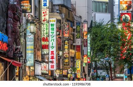 Shinjuku Ward, Tokyo - August 11, 2018 : Late afternoon scene in Kabukicho district. Shops and restaurants neon billboards.