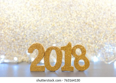 Shiny 2018 numbers with lights and glittery background, New Years Eve concept.