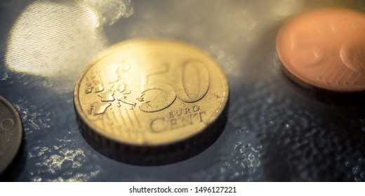 Shiny 50 cents euro coin closeup on a glass table
