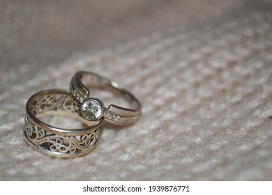 Shiny bijouterie on a neutral knitted background. Diamond ring and patterned silver ring.