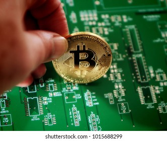 A shiny bitcoin on an electronic board layout background