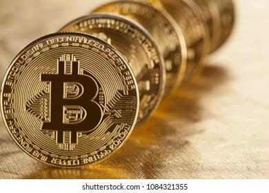 Shiny bitcoins on golden background