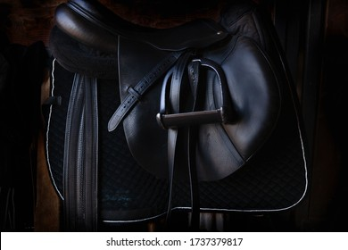 Shiny black leather horse saddle in the dark stable , with stirrup, ready for riding
