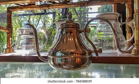 Shiny bronz kettle on pantry shelf