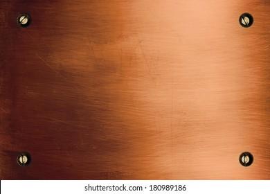 Shiny bronze metallic plate and screws
