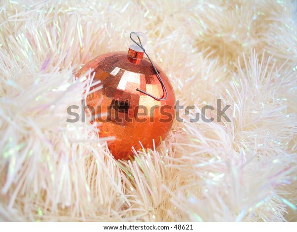 A shiny bulb sitting in a pile of garland.