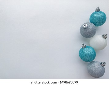 Shiny Christmas balls of blue (turquoise), white, silver color, lie in a row on the right. White background with space for text. The concept of Christmas and holiday eve