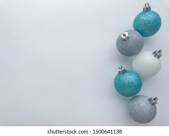 Shiny Christmas balls of blue (turquoise), white, silver color, lie in a row on the right, on a white background with space for text. The concept of Christmas and holiday eve