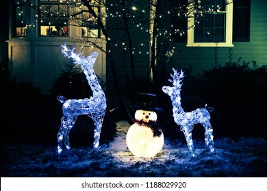 shiny Christmas decorations outside at night. reindeer family and snowman. Christmas background