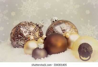 Shiny christmas ornaments laying in a pile of snow with a vintage filtered look