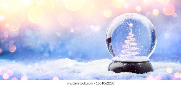Shiny Christmas Tree In Snow Globe On Snow With Golden Lights