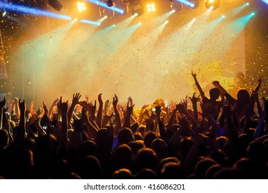 shiny confetti during the concert and the crowd of spectators with their hands up