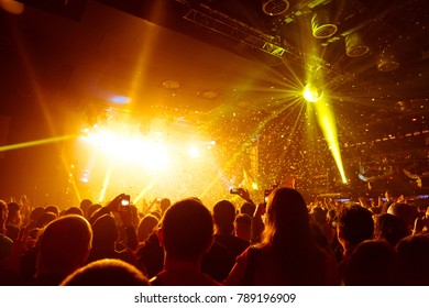 shiny confetti during concert and crowd of spectators with their hands up. tonal correction