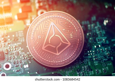 shiny copper AUGUR cryptocurrency coin on blurry motherboard background