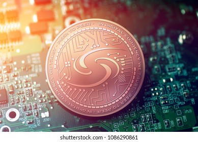 shiny copper SYSCOIN cryptocurrency coin on blurry motherboard background
