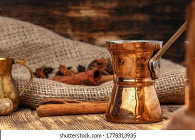 Shiny copper turk with brewed coffee on brown wooden table