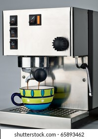 An shiny espresso machine at work, pulling/extracting a fresh coffee shot into a colourful green and blue cup. Quickly becoming a common household appliance.