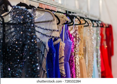 A lot of shiny evening gowns hang in the store