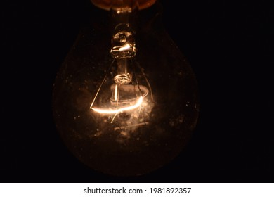 shiny filament of light bulb in dark black background, artistic filament illumination, lighting hot filament coil, An incandescent light bulb, incandescent lamp or incandescent light globe in science.