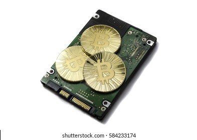 Shiny gold Bitcoin coin laying on hard drive