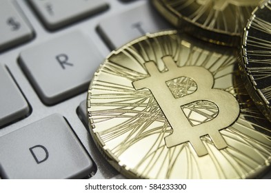 Shiny gold Bitcoin coin laying on white keyboard