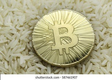 Shiny gold Bitcoin coin laying on chinese rice