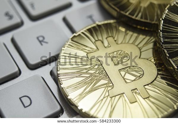 Shiny gold Bitcoin coin laying on white keyboard