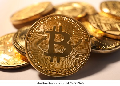 Shiny gold bitcoins on light background, closeup view. Digital currency