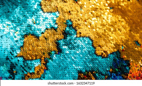 Shiny gold blue sequins background texture backdrop. Light stylish shining spangles pattern. Sequinned material, cloth, pillow fabric closeup macro Earth land and water sea map abstract visual concept