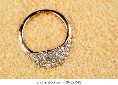 A shiny gold ring with cubic zirconia (diamond substitute) in sand