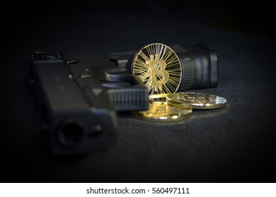 Shiny gold virtual currency bitcoin with gun on black background