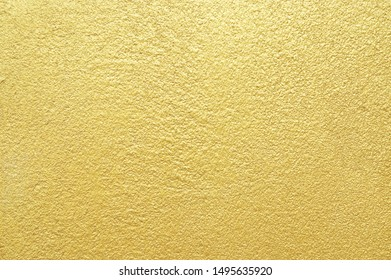 Shiny golden background. Gold wall texture. Abstract seamless wallpaper.